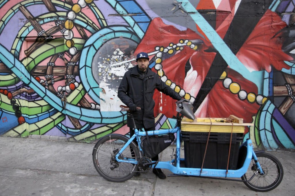Diego Gerena-Quiñones stands with his delivery service cargo bike in front of a NYC mural.