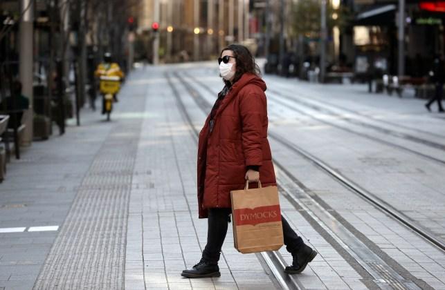 A woman crosses a busy street in Sydney.