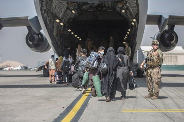 families begin to board a U.S. Air Force Boeing C-17 Globemaster III during an evacuation at Hamid Karzai International
