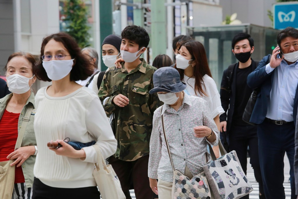 People wearing face masks to protect against the spread of the coronavirus walk on a street in Tokyo Monday, Aug. 16, 2021.