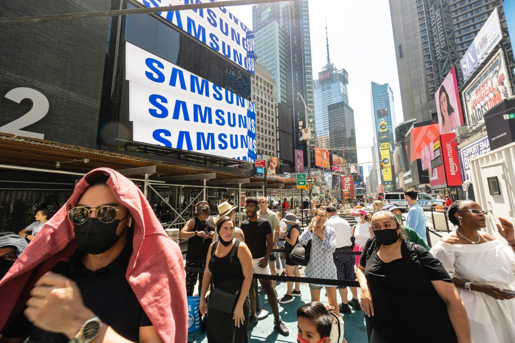 Ticket buyers wait in 90-degree heat to ride the Times Square Wheel on opening day.