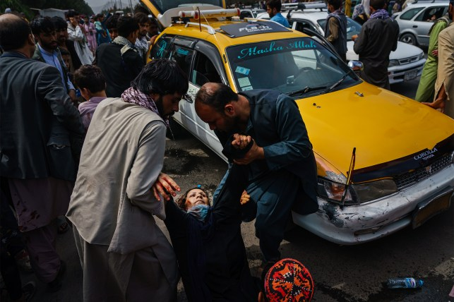 Men try to help a wounded woman and her injured child as Taliban fighters use guns, whips, sticks and sharp objects to maintain crowd control over thousands of Afghans waiting for their way out of Kabul Airport. Keep doing  , Afghanistan, Tuesday, August 17, 2021.  Within an hour of the escalating violence, at least half a dozen people were injured, including a woman and her child.