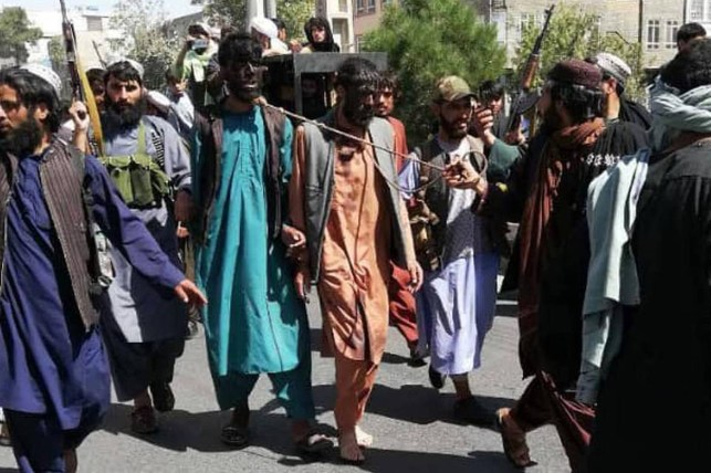 """Men parade through the streets of Herat with the Taliban - even leaders have promised a government. """"Positively different."""""""