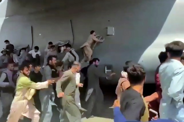 Hundreds of people run with the US Air Force's C-17 transport plane, some boarding the plane, as it operates under the runway of the international airport, in Kabul, Afghanistan.