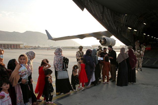 Afghans board on a Qatari transport plane at Hamid Karzai International Airport in Kabul, Afghanistan on August 18, 2021.