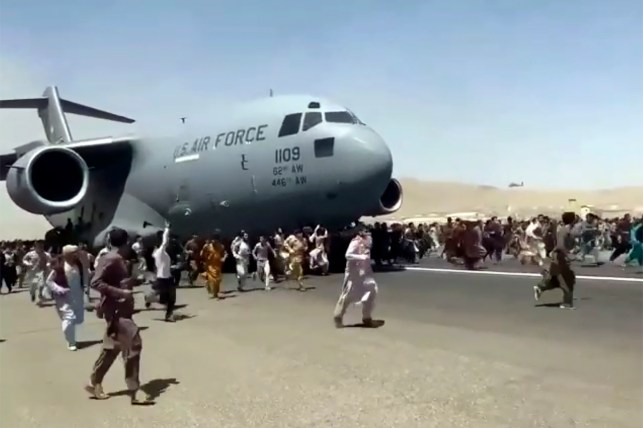Hundreds of people are running down the runway of Kabul International Airport on August 16, 2021, with a US Air Force C-17 transport aircraft.