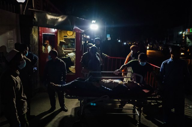 Hospital staff helps bring in a wounded patient brought by an ambulance at EMERGENCY Hospital in Kabul, Afghanistan, Thursday, Aug. 26, 2021. Twin bombings struck near the entrance to Kabul's airport Thursday, ripping through crowds of Afghans and foreign nationals waiting for evacuation from the country. The explosions complicated an already-nightmarish airlift just before the U.S. deadline to remove its troops from the country.