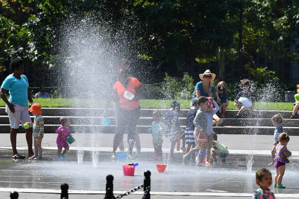 Kids playing at water sprinkles inside the Cadman Plaza Park in downtown Brooklyn amid a historic heat wave in NYC.
