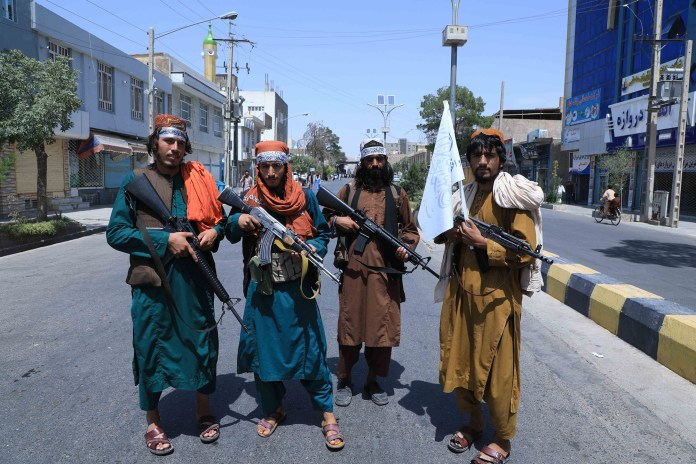 Four Afghan citizens holding guns.