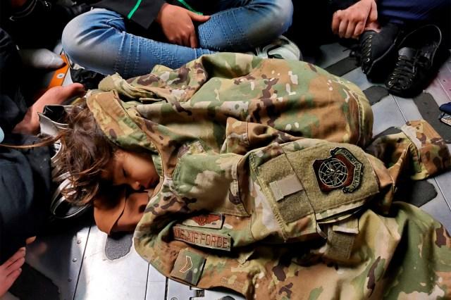 An Afghan child sleeps on the cargo floor of a U.S. Air Force C-17 Globemaster III.