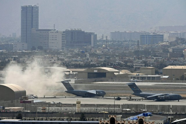 S soldiers stand on the tarmac as an US Air Force aircraft (L) prepares for take off from the airport in Kabul on August 30, 2021
