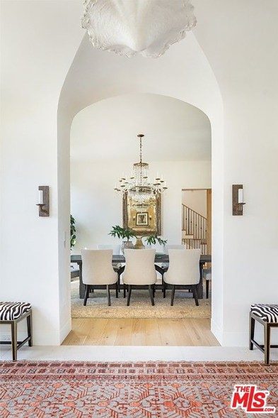 A dining room is visible through an arched doorway.