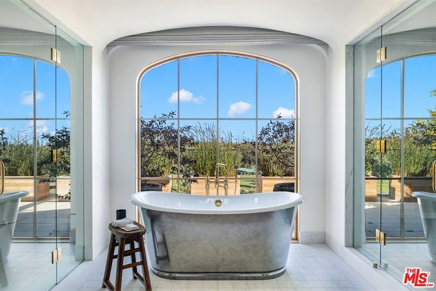 A luxurious standalone tub is pictured in front of an arched window.