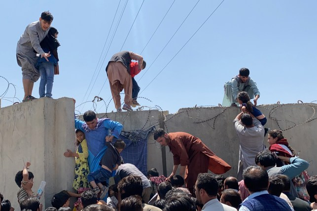 People are trying to leave the country from the top of the wall outside the airport from Kabul on August 16, 2021.