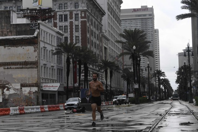 A man runs on Canal Street in New Orleans, Louisiana, on August 30, 2021.