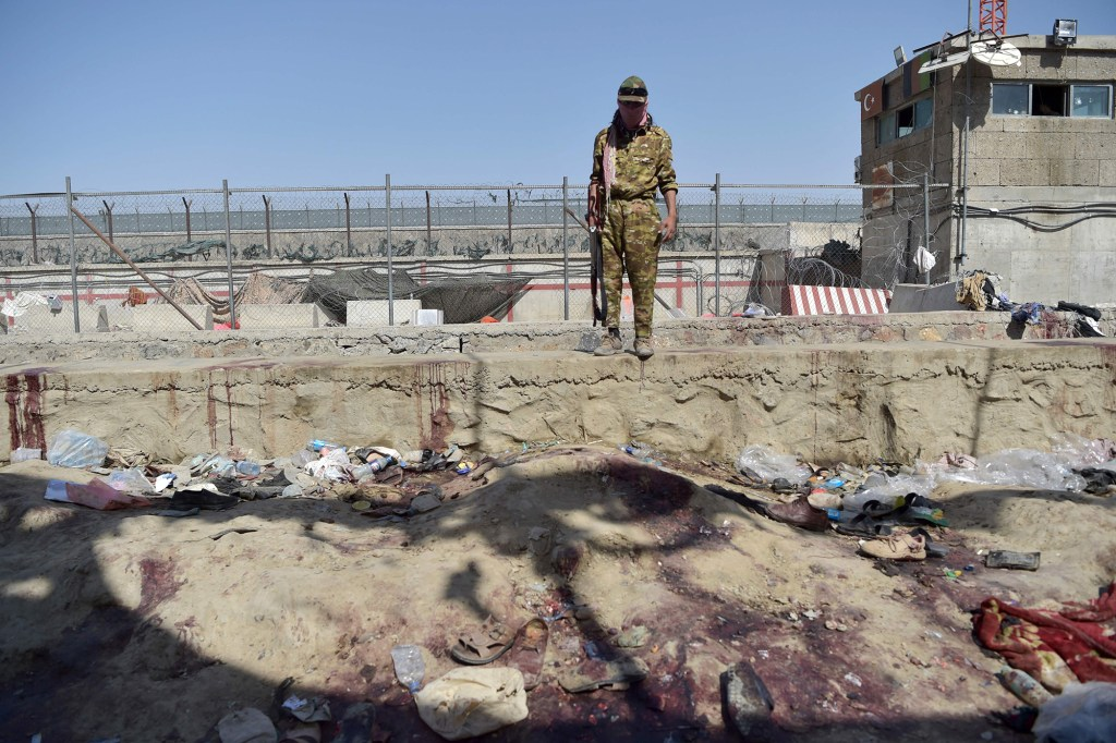A Taliban fighter stands guard at the site of two powerful explosions, which killed scores of people including 13 US troops;