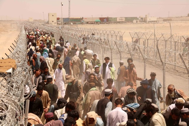 People stranded at the Pakistani-Afghan border wait to cross after it was reopened at Chaman, Pakistan on August 13, 2021.