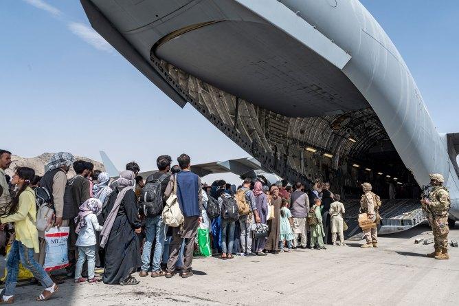 U.S. Airmen and U.S. Marines guide evacuees aboard a U.S. Air Force C-17 Globemaster III in support of the Afghanistan evacuation at Hamid Karzai International Airport in Kabul, Afghanistan.