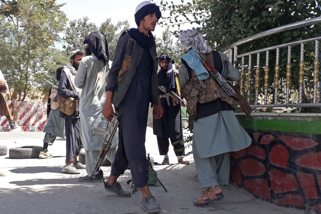 Taliban fighters stand along the roadside in Ghazni on August 12.