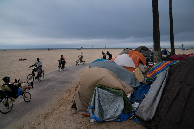 People riding bikes past a homeless encampment in Venice, Los Angles on June 29, 2021.
