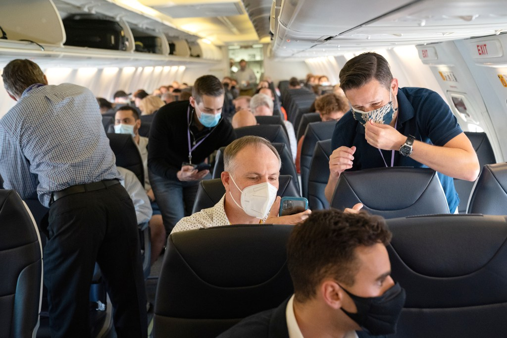 Passengers wearing protective masks on a plane.