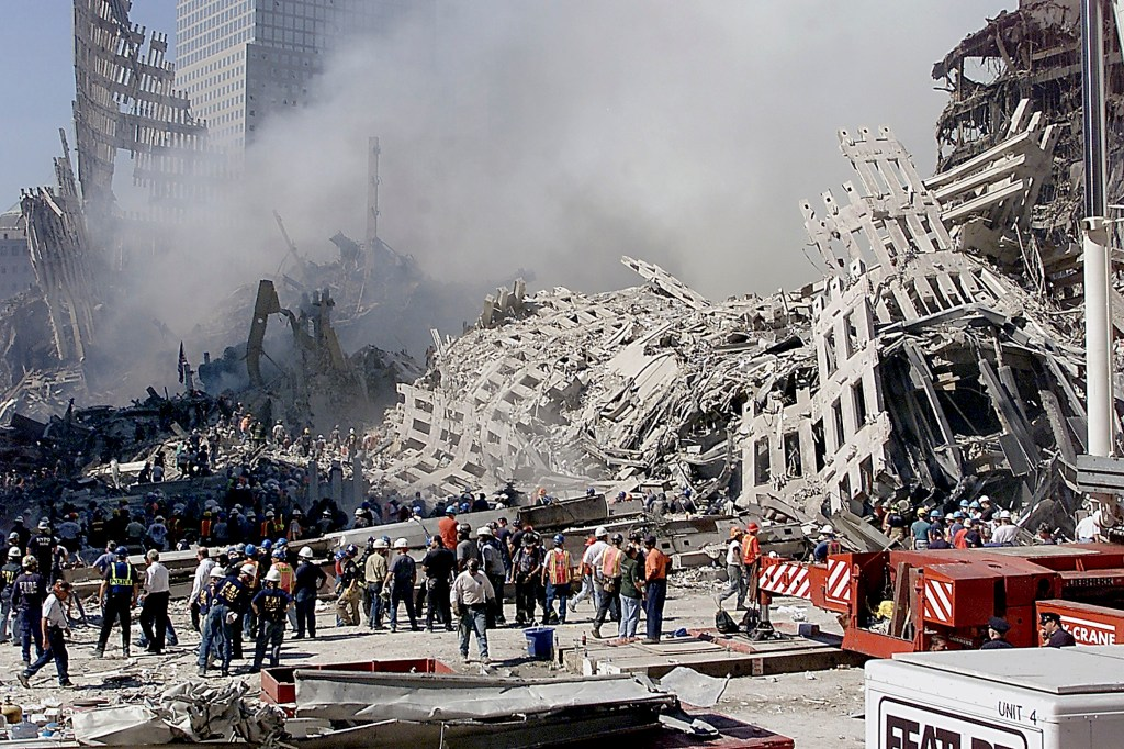 Fire and rescue workers search through the rubble of the  World Trade Center 13 September 2001 in New York. Rescue and cleanup continues after the twin towers were destroyed 11 September 2001 by terrorist in hijacked commercial aircraft.