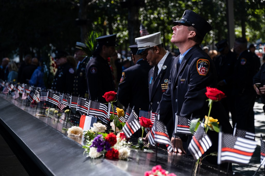 FDNY members mourn at the 9/11 memorial reflecting pools during the 20th anniversary ceremony of the September 11 terrorist attacks.