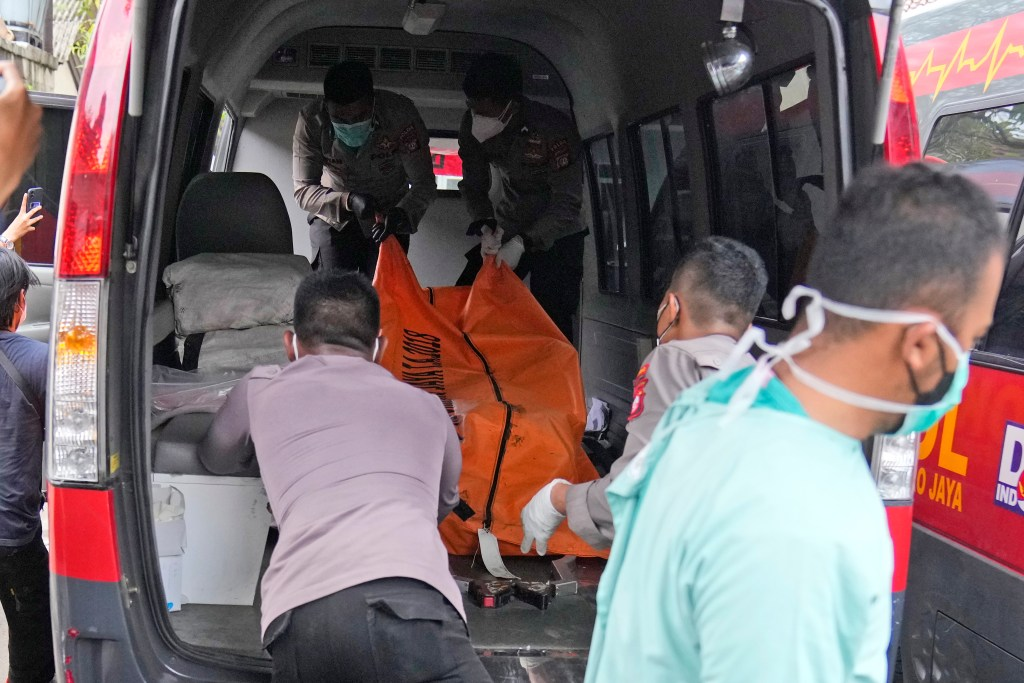 Officers load a body bag containing the body of a victim of a prison fire to be transferred to the national police hospital for identification.