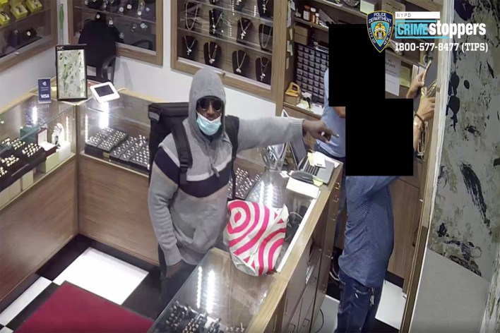 Surveillance footage captures the suspect in the midst of robbing Prince Street Jewelers in Brooklyn on Sept. 7, 2021.