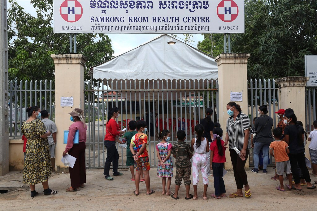Children wait in front of Samrong Krom health center outside Phnom Penh, Cambodia, before their receive a shot of the Sinovac's COVID-19 vaccine Friday, Sept. 17, 2021.