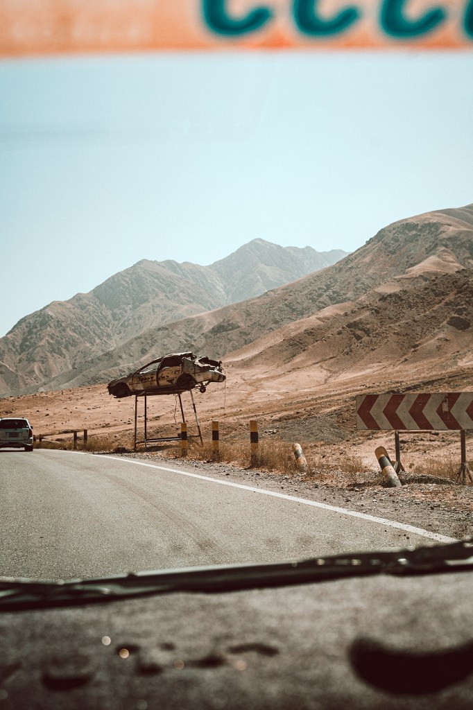 A destroyed car is hoisted up on bars to remind Afghan drivers to take it easy on the roads.