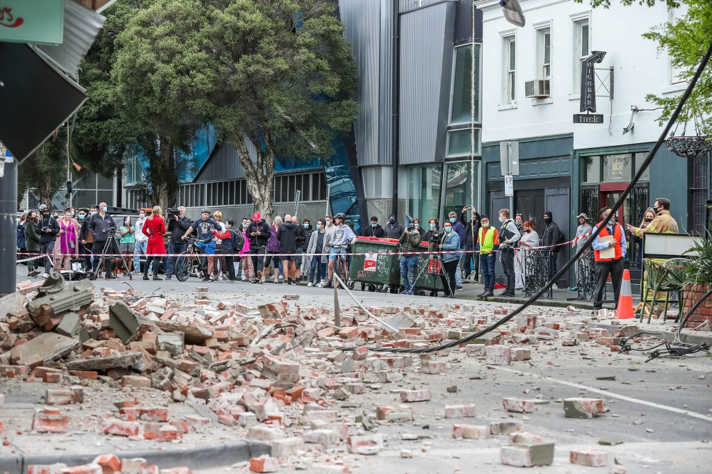 Bystanders observe the damage left by Wednesday's earthquake.