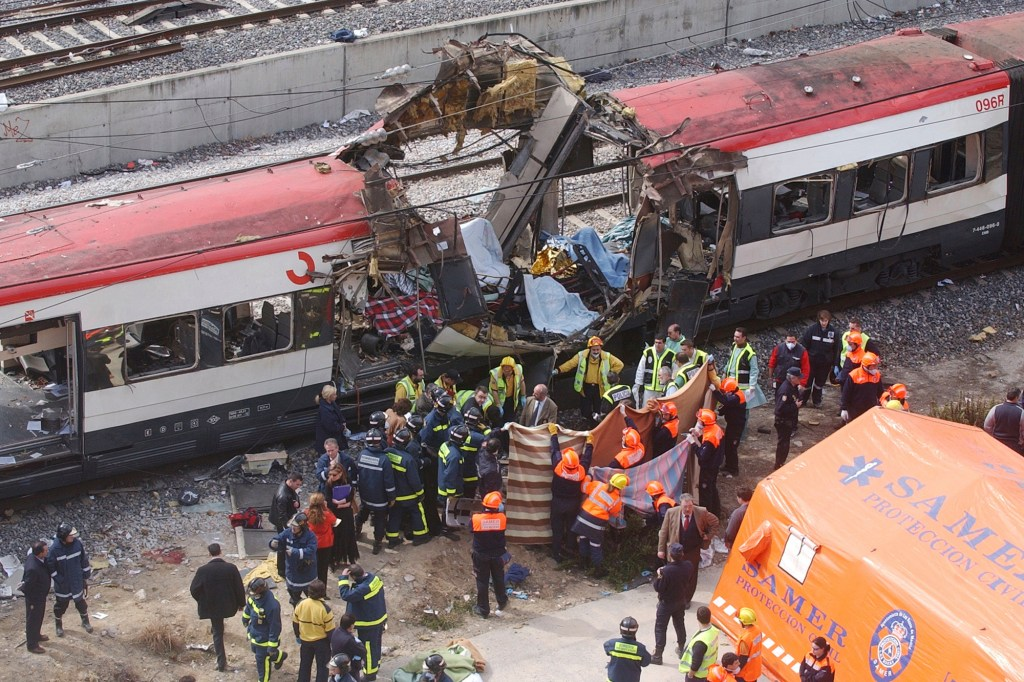 In this March 11, 2004 file photo rescue workers cover up bodies alongside a bomb-damaged passenger train, following a number of explosions in Madrid, Spain, March 11, 2004.