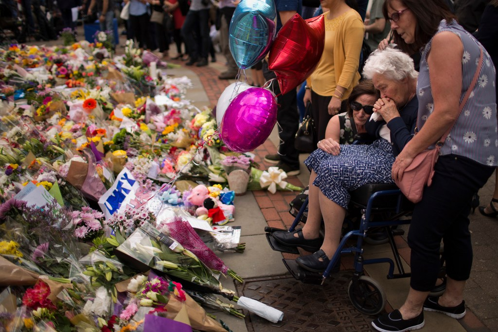 In this May 24, 2017 file photo women cry after placing flowers in a square in central Manchester, Britain, after the suicide attack at an Ariana Grande concert that left more than 20 people dead and many more injured, as it ended on Monday night at the Manchester Arena.