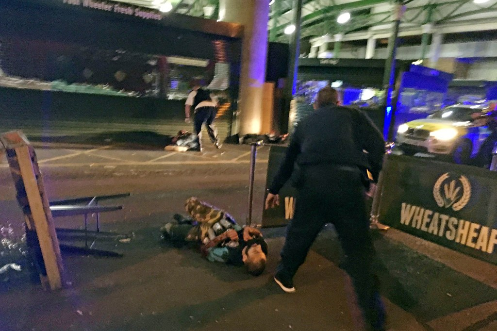 In this image provided by Gabriele Sciotto taken on Saturday, June 3, 2017, one of the suspects from the London Bridge attack, wearing what appear to be canisters strapped to his chest, lies on the ground after being shot by police outside Borough Market in London. In the 20 years since the Sept. 11, 2001 terrorist attacks in the United States, a mixture of homegrown extremists, geography and weaknesses in counterterrorism strategies have combined to turn Europe into a prime target for jihadists bent on hurting the West.