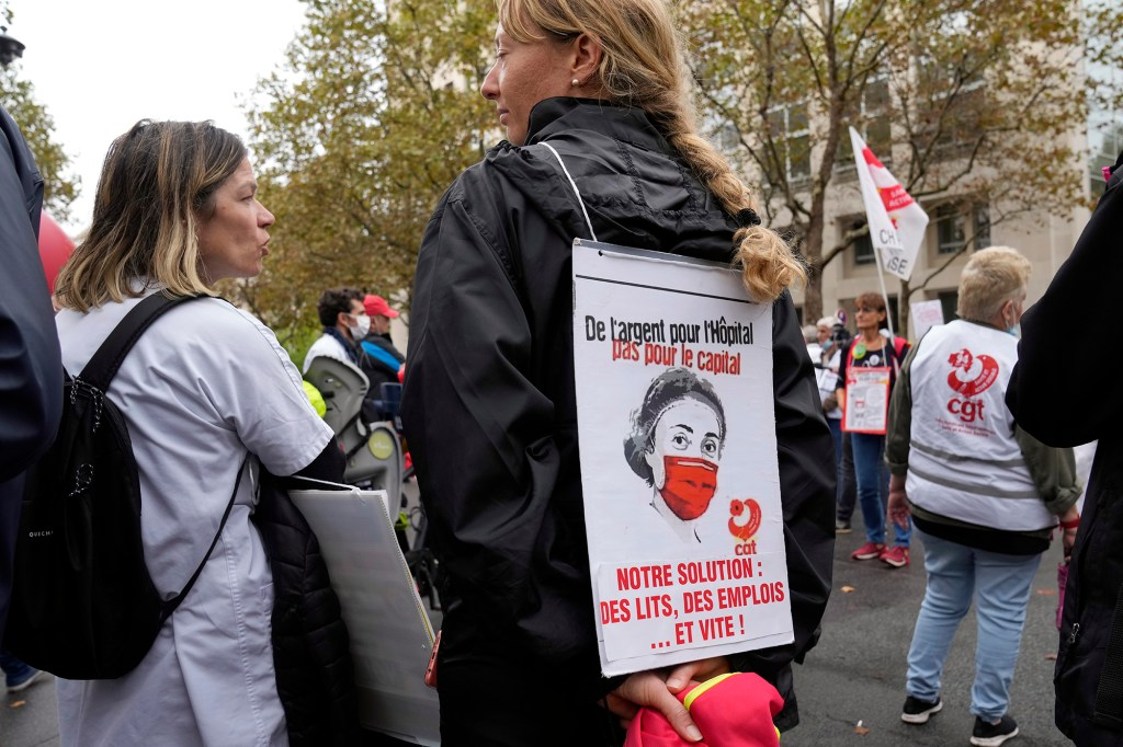 """A medical worker holds a placard reading : """"Money for Hospital, Not for the Capital, Our Solution Hospitals beds, Employs and quick"""", during a protest gathering outside the Health Ministry, in Paris, Tuesday, Sept. 14, 2021 against a law requiring them to get vaccinated by Wednesday or risk suspension from their jobs."""