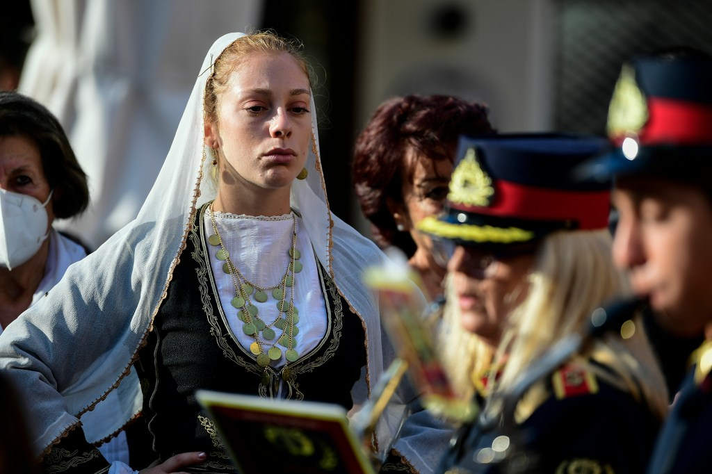 A woman in traditional dress from the island of Crete attends a procession, ahead of the burial of the late Greek composer Mikis Theodorakis in Chania, Crete island, Greece, Thursday, Sept. 9 2021.