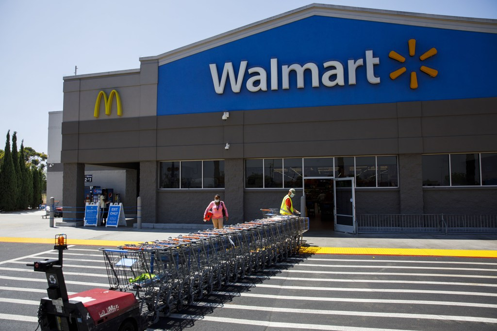 Exterior of a Walmart store with shopping carts lined up at the entrance.