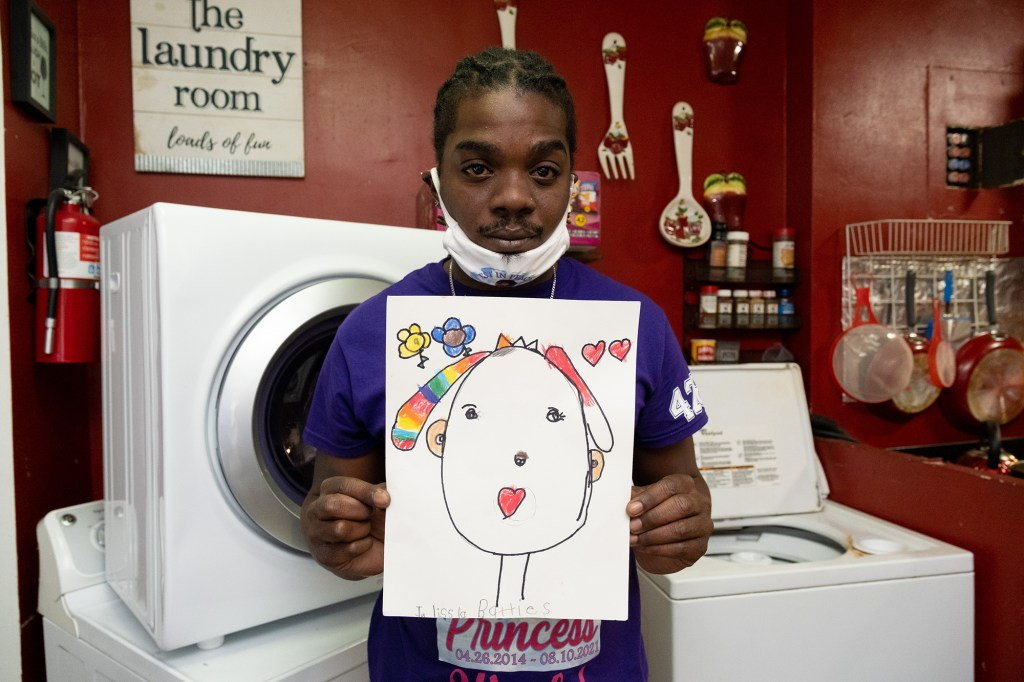 Julius Batties, father of Julissa Batties who was killed by abdominal trauma at the age of 7 on August 10th, 2021, holds a school drawing by her.
