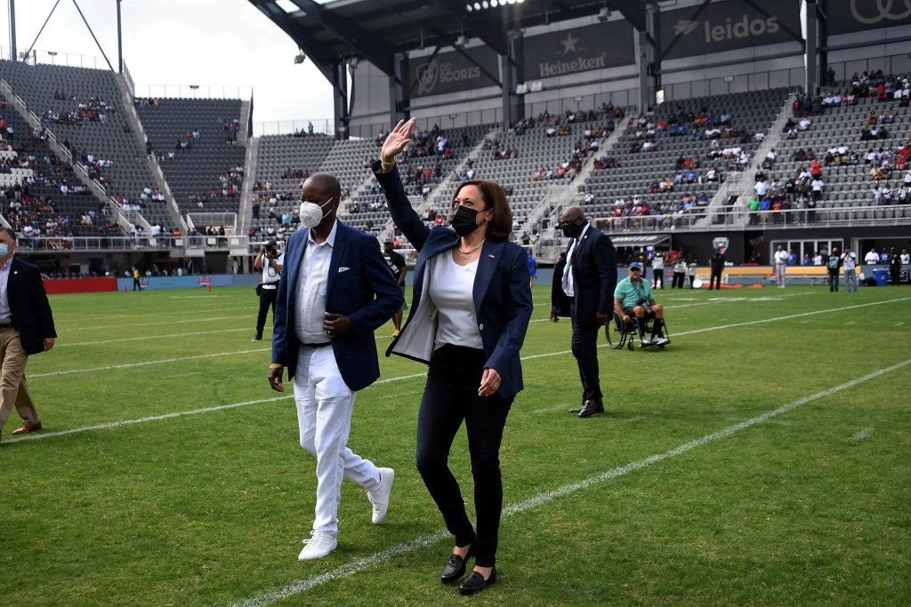 Vice President Kamala Harris, with Howard University President Wayne A. I. Frederick (L), waves as she leaves the field after tossing the coin for the football game between Howard University and Hampton University at Audi Field in Washington, DC on September 18, 2021.