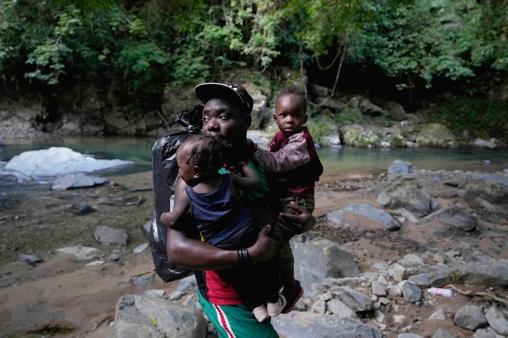 A migrant carries two children across a river as they continue their trek north, near Acandi, Colombia, Wednesday, Sept. 15, 2021.