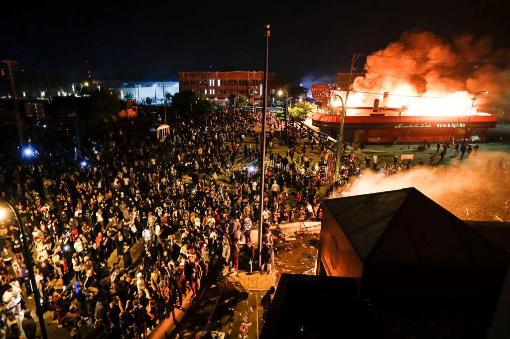 Protestors gather outside a burning city district beside the Minneapolis 3rd Police Precinct in Minnesota on May 28, 2020.