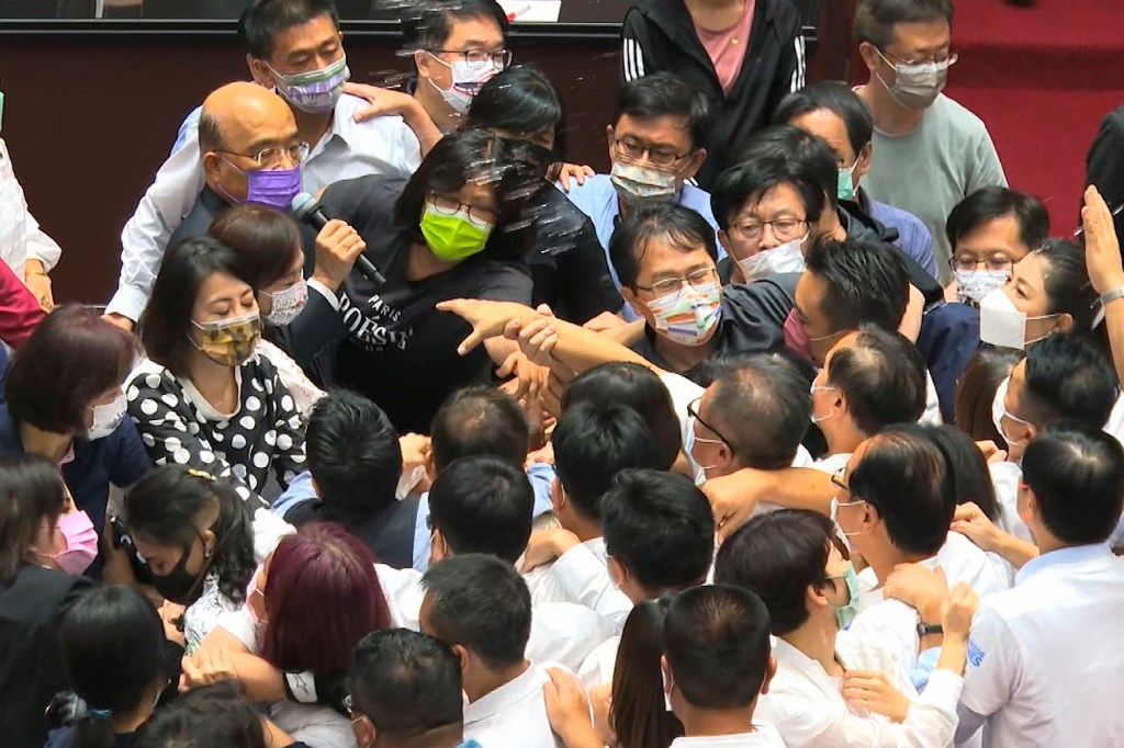 In this image taken from video by Taiwan's EBC, Premier Su Tseng-chang, in purple mask, tries to make a policy speech amid a scuffle between opposition Nationalist party and ruling Democratic Progressive Party lawmakersduring a parliament session in Taipei, Taiwan, Tuesday, Sept. 28, 2021.