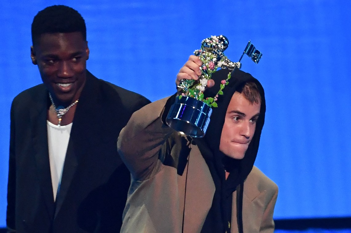 """Justin Bieber celebrates his Best Pop win for """"Peaches"""" alongside Giveon at the 2021 VMAs."""