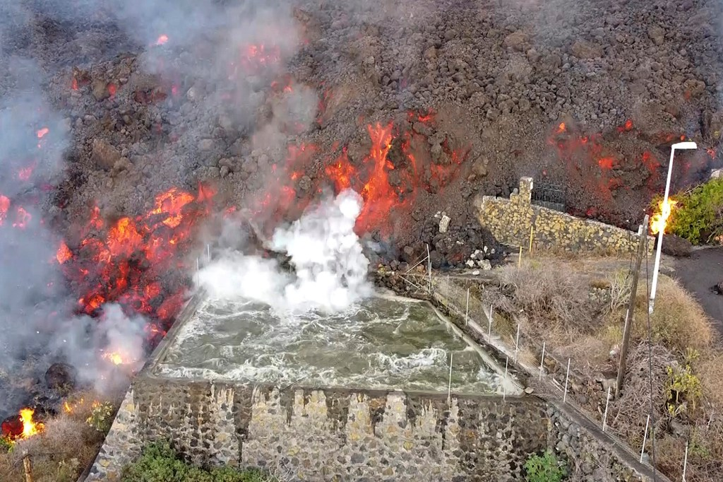 In this Monday Sept. 20, 2021 file photo, hot lava reaches a balsa normally used for for irrigation after an eruption of a volcano on the island of La Palma in the Canaries, Spain.