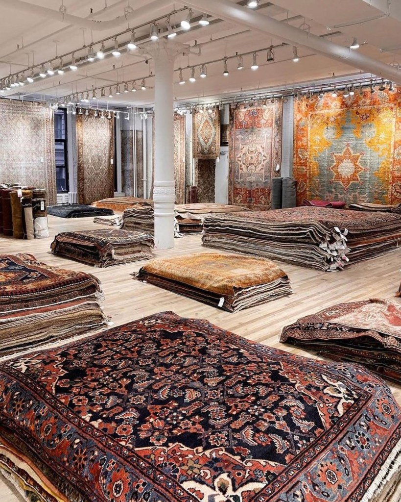 A display of rugs hanging and piled on the floor at ABC Carpet & Home.