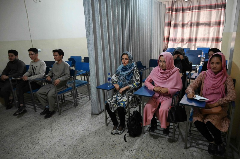 Male and female students attending a class are separated by a curtain at a private university in Kabul.