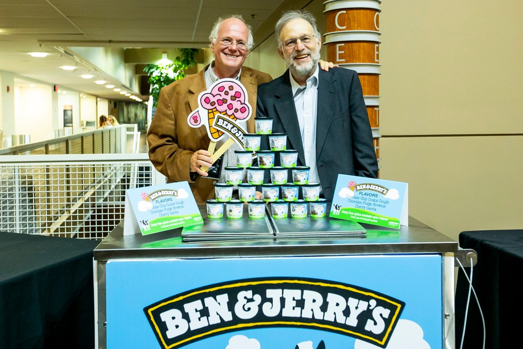 Ben Cohen and Jerry Greenfield, co-founders of the Ben & Jerry's ice cream company standing behind a table filled with some of their products