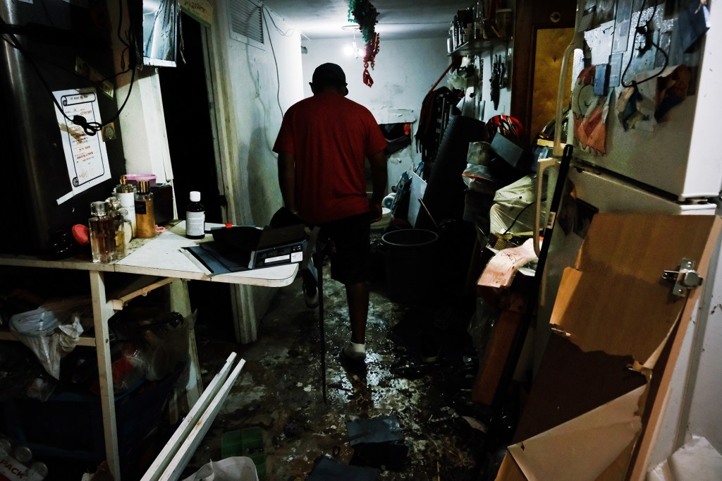 Eddie, an immigrant from Mexico, walks through his flooded basement level apartment in Queens following this week's storm.