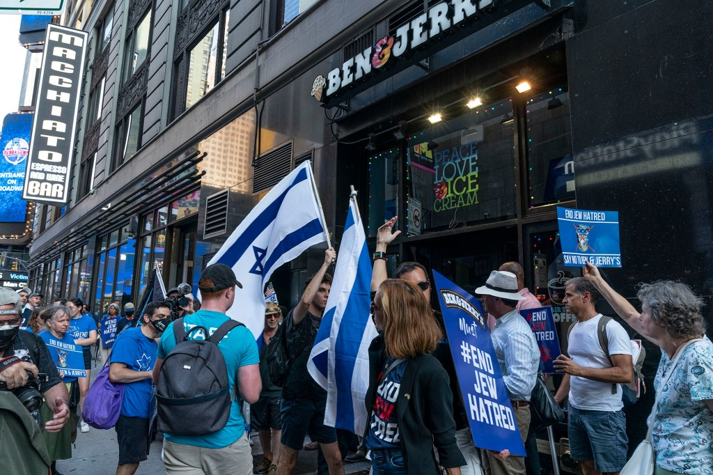 A group of protestors waving the Israeli flag outside a Ben & Jerry's store.